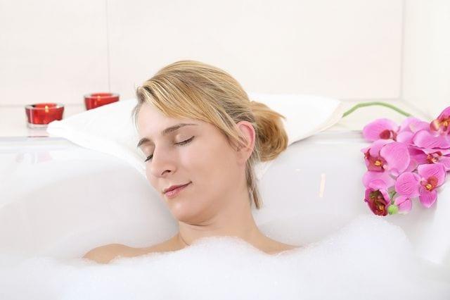 Frau nimmt ein entspannendes Bad im Rahmen einer Wärmetherapie.