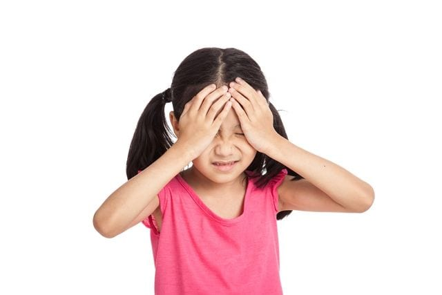 Kind mit Kopfschmerzen aufgrund Vitmain D-Mangels