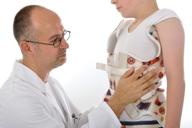 Arzt legt eine Korsett bei einem Kind an aufgrund einer Wirbelsäulenverkrümmung