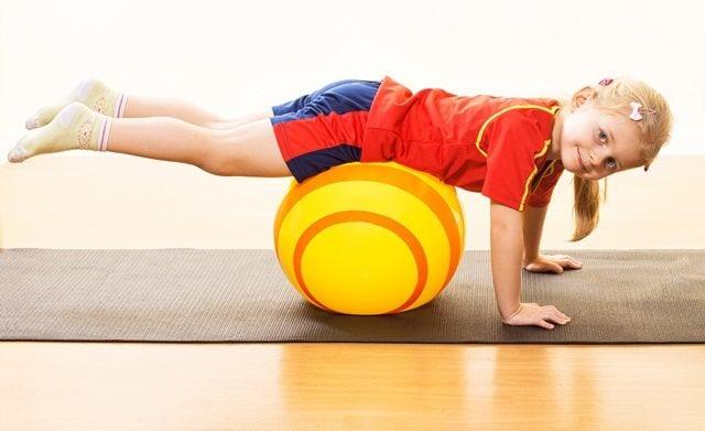 Kind mit Rückenschmerzen hat Spaß bei Krankengymnastik
